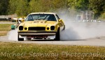 Dennis Repel (Chevy Camaro) lays down a smoke screen in Turn 2 in an (unsuccessful) attempt to confuse Mark Brown (Lotus Seven S3) - Michael Stanway photo