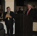 Dennis Repel accepts Pegasus Award on behalf of winner Geoff Tupholme and then learns that Geoff will be in the 1:18's in 2012 - J. Backe photo