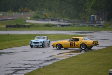 Whoops! Even 'Detroit Iron' is spooked by a 'Big Healey'! Dennis Repel (1974 Chevrolet Camaro) does a graceful pirouette in front of Ivan Lessner (1958 Austin Healey 100-6) leaving Turn 1. Dennis eventually recovered to win the race. - Glen Gibbons photo